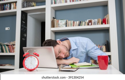 Portrait of tired student sleeping in library on his laptop computer. Close-up of red alarm-clock.