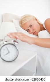 Portrait of a tired woman awaken by an alarmclock in her bedroom