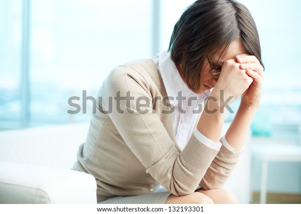 Portrait of tired woman touching her head