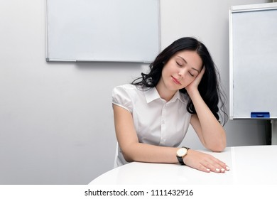 Portrait of tired young businesswoman sitting with closed eyes at workplace. Pretty girl in business clothes relaxing at white desktop. Place for text