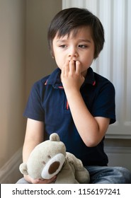 Portrait of toddler boy biting his finger nails and looking out with thnking face, Sad Child sitting with teddy bear looking down and puting fingers in his mouth, Childhood and family concept