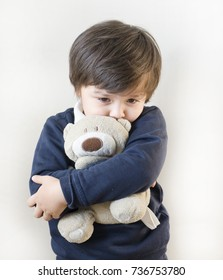 Portrait of toddler boy hugging teddy bear with sad face and looking down, Unhappy child concept