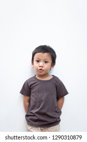Portrait of a toddler boy with puckering facial expression on white background
