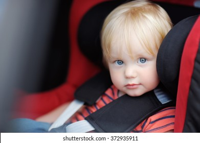 Portrait of toddler boy sitting in car seat