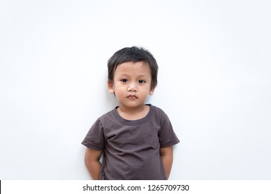 Portrait of a toddler boy wearing grey T-shirt on white background