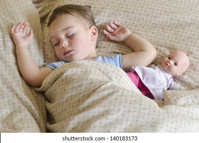 Portrait of toddler child,  boy or girl, sleeping in a bed with a toy doll.