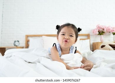 Portrait of a toddler girl 3 years old waking up and puckering facial expression in bed