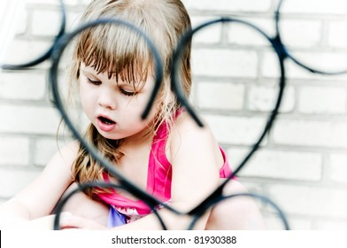 Portrait of the toddler girl in improvised heart-shaped frame