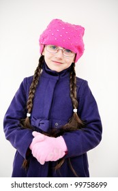 Portrait of toddler girl with pigtail in pink barret and purple coat, isolated on white background