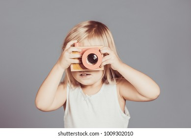 Portrait of toddler girl taking photo using wooden camera toy