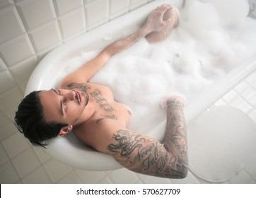 Portrait from the top of a man having a bath in a tub full of foam