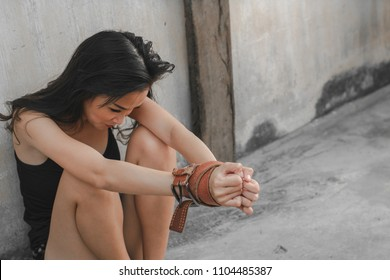 Portrait torture, depressed beautiful woman: Attractive girl feels sad, scared, fears or hopeless. Pretty poor girl tie leather belt on her arms by traffickers, kidnapper. She is crying. She is victim