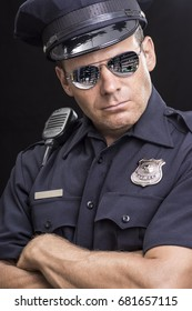 Portrait of tough and serious Caucasian police officer wearing reflective sunglasses and crossing arms on black background