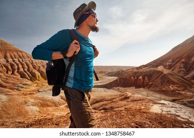 Portrait of Tourist with backpack and hat at the surreal red mountains background against blue sky