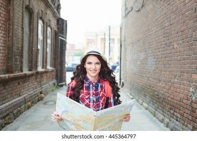 Portrait of a tourist girl in a hat holding a map and looking at her in the alley buildings of red brick