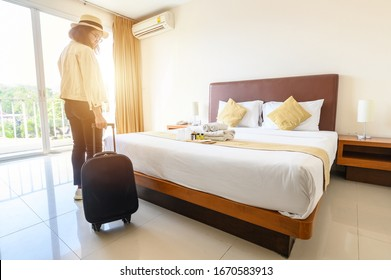 Portrait of tourist woman with her luggage after check-in hotel bedroom. Conceptual of travel and vacations.