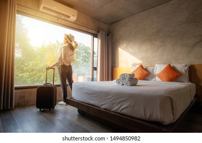 Photo of Portrait of tourist woman standing nearly window, looking to beautiful view with her luggage in hotel bedroom after check-in. Conceptual of travel and vacation.