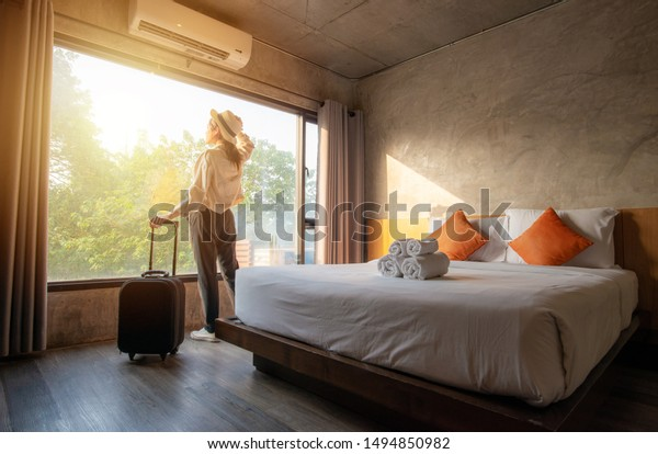 Portrait of tourist woman standing nearly window, looking to beautiful view with her luggage in hotel bedroom after check-in. Conceptual of travel and vacation.