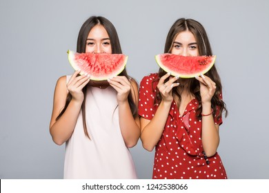 Portrait of tourists ladies having lobes of watermelon in hands, isolated on white background