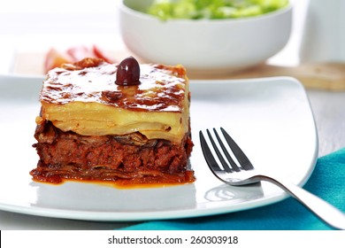 portrait of Traditional Greek beef Moussaka with olive served in dish with fork aside
