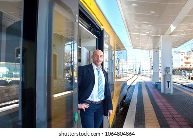 Portrait of the train conductor middle aged waiting passengers to board. Modern train at the European station in summer.