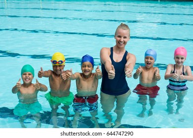 Portrait of trainer and children showing thumbs up in swimming pool