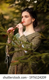 Portrait of Tranquil Caucasian Brunette Female in Old Medieval Green Dress With Flute Against Firtrees Outdoors.Vertical Image