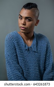 Portrait of transgender woman standing over gray background