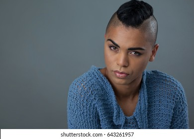 Portrait of transgender woman wearing blue sweater over gray background