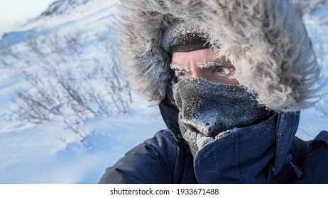 Portrait of a traveler in the Arctic. A man in winter clothes, a hood and a mask. Ice on the eyebrows and eyelashes. Extremely cold weather in the far north in the Arctic. Travel to the polar region.