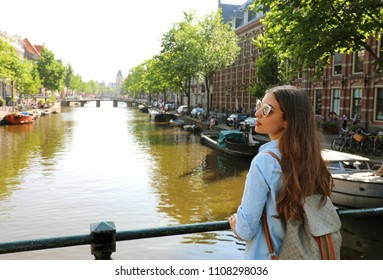Portrait of traveler girl with sunglasses and backpack enjoying Amsterdam city. Back view of young woman looking to the side on Amsterdam channel, Netherlands, Europe.