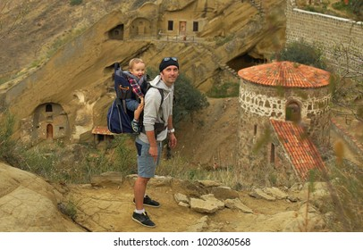 Portrait of travler with small son sitting in baby carrier backpack on background of David Gareja monastery complex, Georgia