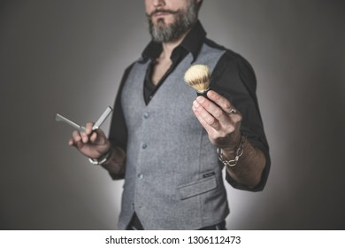 portrait of a trendy barber with a black shirt and a waistcoat holding classic shaving tools in his hands