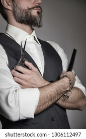 portrait of a trendy barber with a white shirt and waistcoat holding classic hair-cutting tools in his hands
