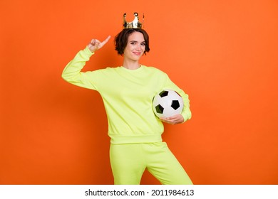 Portrait of trendy beautiful cheery girl holding in hand ball demonstrating tiara isolated over bright orange color background
