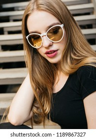 Portrait of trendy casual young woman in black wear and sunglasses with long blond hair posing near urban wall along