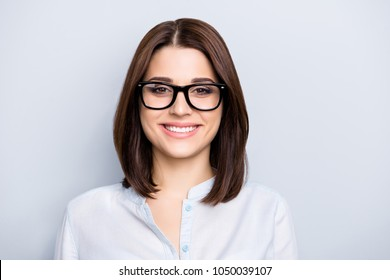 Portrait of trendy, caucasian, cheerful, modern, nice, stylish, cute, clever girl in eyewear isolated on grey background, looking at camera