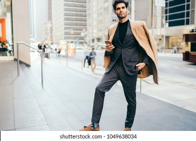 Portrait of trendy dressed male entrepreneur standing on avenue in New York downtown holding mobile hone, handsome man in stylish outfit looking at camera using smartphone for checking mail