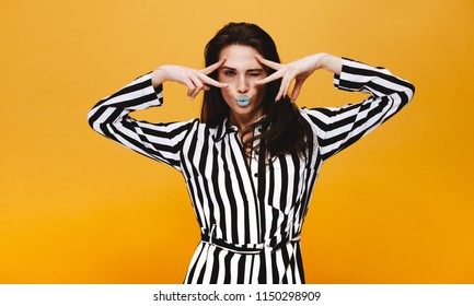 Portrait of trendy female model standing against orange background. Woman with artistic makeup winking with puckered lips.