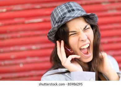 Portrait of trendy girl shouting on the phone