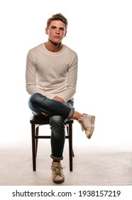 Portrait of a trendy guy wearing long-sleeve shirt sitting on cheir against white wall