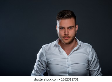Portrait of a trendy handsome guy wearing white shirt while posing in studio
