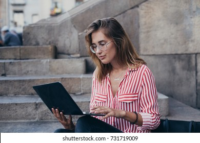 Portrait of trendy millennial hipster woman sits on stairs of university, works on laptop outdoors, freelance or out of office day, lunch break business woman always connected
