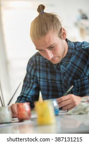 portrait of a trendy young man sitting in his home and making a painting, there are color paint cans on the table