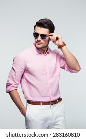 Portrait of a trendy young man in sunglasses and pink shirt over gray background