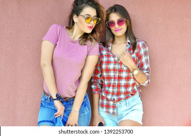 Portrait of trendy young woman friends wearing fashionable sunglasses and casual clothes jeans shorts plaid shirt smiling at camera standing over pink wall
