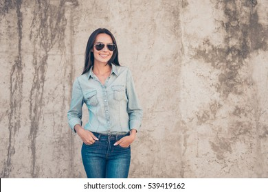 Portrait of trendy young woman in glasses standing near stone wall