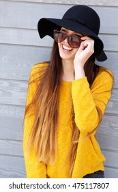 Portrait of trendy young woman wearing sunglasses and hat