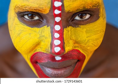 portrait of an tribal African woman painted yellow  face , frontal view
