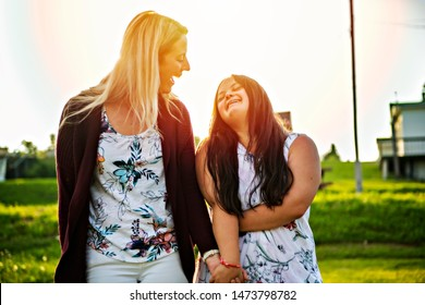 A Portrait of trisomie 21 adult girl smilin outside at sunset with family friend